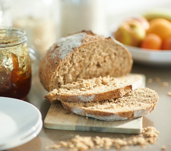 Sliced wheat bread next to a jar of jam.