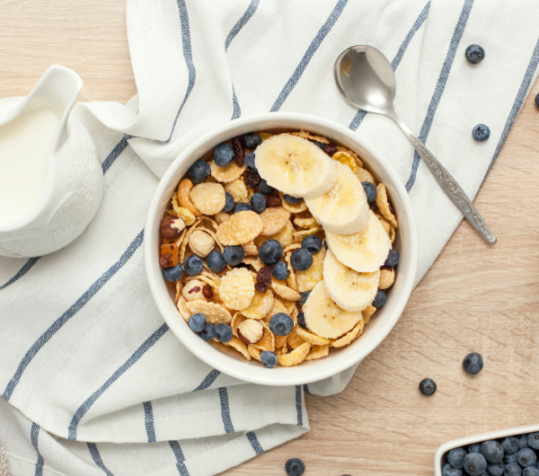 A bowl of bran cereal covered in blueberries and bananas on top of a white and blue striped towel.