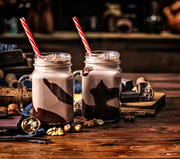Two chocolate milkshakes in mason jars with red and white striped straws sitting on a wooden table.