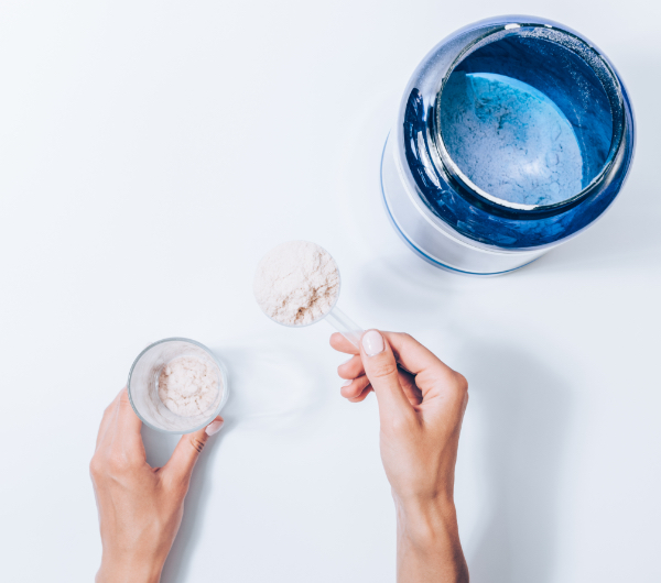 hands scooping powder from blue jar into glass