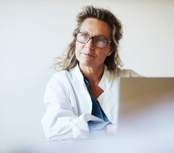 woman with glasses gazing up from laptop