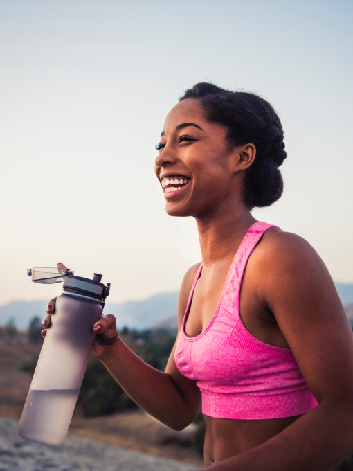 A woman with a water bottle smiling.