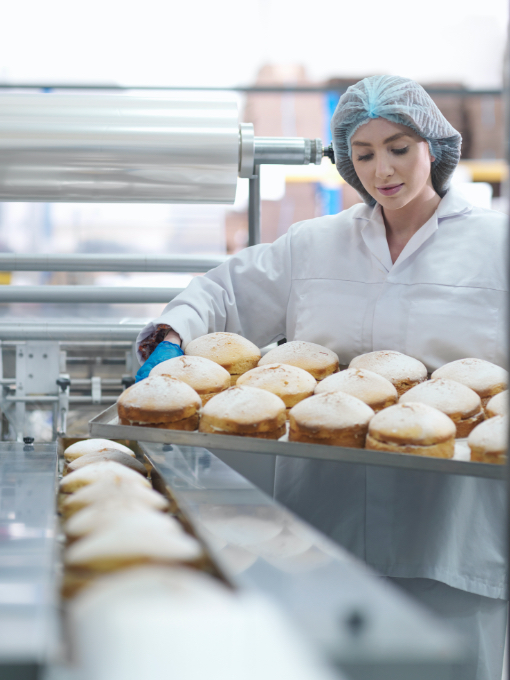 A woman inspecting a tray of bread in a factory.